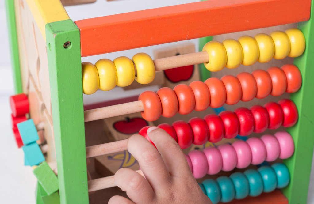 Child learning simple math and colors through abacus